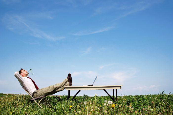 Man-relaxing-in-field-700x467